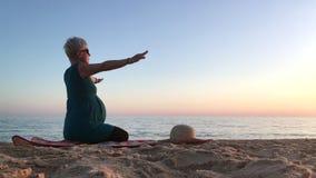 Mujer en el noveno mes del embarazo excercising en la playa almacen de metraje de vídeo