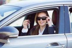 Mujer en el nuevo coche con llaves Fotografía de archivo libre de regalías