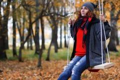 Mujer en el oscilación en parque del otoño Fotografía de archivo