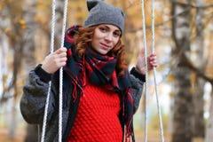 Mujer en el oscilación en parque del otoño Imagenes de archivo