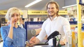 Mujer en el pago y envío del supermercado, ella está pagando usando una tarjeta de crédito almacen de video