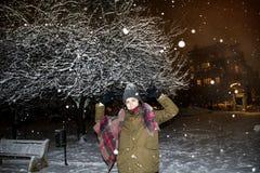 Mujer en el parque del invierno por noche durante las nevadas Imagen de archivo