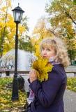 Mujer en el parque del otoño imagenes de archivo