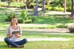 Mujer en el parque usando su ordenador de la tablilla Fotografía de archivo libre de regalías