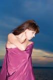 Mujer en el perfil cubierto con la presentación púrpura del paño Fotos de archivo libres de regalías