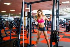 mujer en el peso de elevación de la pesa de gimnasia del gimnasio Fotografía de archivo