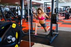 mujer en el peso de elevación de la pesa de gimnasia del gimnasio fotos de archivo libres de regalías