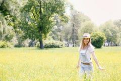 Mujer en el prado con las flores amarillas Foto de archivo libre de regalías