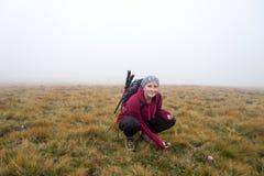 Mujer en el prado de las montañas en la niebla imagen de archivo