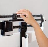 Mujer en el primer de la escala del peso Foto de archivo libre de regalías