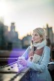 Mujer en el puente de Brooklyn que mira Manhattan con un café foto de archivo libre de regalías