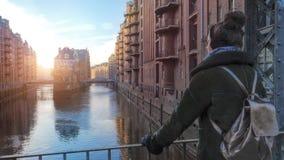Mujer en el puente a través del canal en distrito viejo del almacén en Hamburgo imagen de archivo