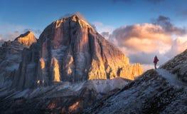 Mujer en el rastro que considera en pico de alta montaña la puesta del sol foto de archivo