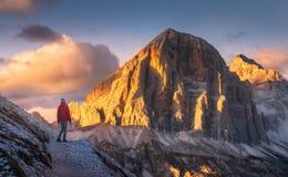 Mujer en el rastro que considera en pico de alta montaña la puesta del sol imagen de archivo libre de regalías