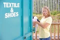 Mujer en el reciclaje del centro que dispone de la ropa Imágenes de archivo libres de regalías