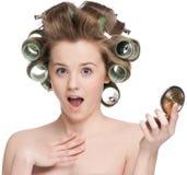 Mujer en el rodillo del pelo que mira en espejo Foto de archivo libre de regalías