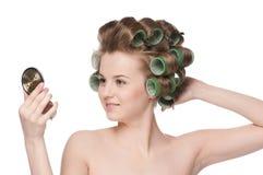 Mujer en el rodillo del pelo que mira en espejo Imagen de archivo