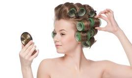 Mujer en el rodillo del pelo que mira en espejo Imagen de archivo libre de regalías