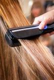Mujer en el salón de belleza que endereza el pelo Fotos de archivo libres de regalías