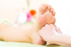 Mujer en el salón del clavo que recibe masaje del pie Imagen de archivo libre de regalías
