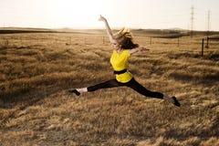 Mujer en el salto de Balet en un campo Imagen de archivo libre de regalías
