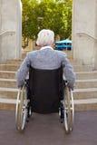Mujer en el sillón de ruedas que mira Fotos de archivo