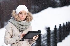 Mujer en el smartphone de la tableta en parque del invierno en un fondo de Imagen de archivo