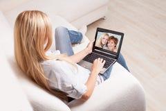 Mujer en el sofá con el ordenador portátil Imagen de archivo libre de regalías