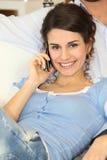 Mujer en el sofá con el teléfono celular Fotografía de archivo libre de regalías