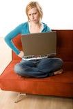 Mujer en el sofá con la computadora portátil Imágenes de archivo libres de regalías