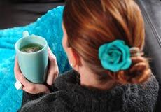 Mujer en el sofá con la manta y la taza de té Foto de archivo libre de regalías