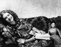 Mujer en el sofá con las muñecas (todas las personas representadas no son vivas más largo y ningún estado existe Garantías del pr foto de archivo libre de regalías