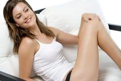 Mujer en el sofá en ropa de sport Foto de archivo