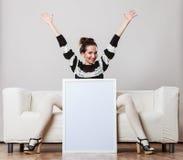 Mujer en el sofá que lleva a cabo al tablero de la presentación en blanco Imagen de archivo libre de regalías