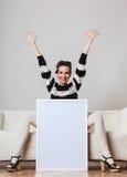 Mujer en el sofá que lleva a cabo al tablero de la presentación en blanco Foto de archivo libre de regalías