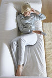 Mujer en el sofá que ve la TV Fotos de archivo libres de regalías