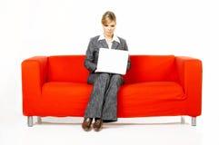 Mujer en el sofá rojo foto de archivo libre de regalías