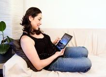 Mujer en el sofá con el ordenador de la radio de la tablilla del iPad Imagenes de archivo