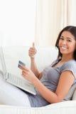 Mujer en el sofá que trabaja con el cuaderno con el pulgar para arriba Foto de archivo