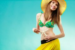 Mujer en el sombrero amarillo que lleva a cabo la cáscara blanca foto de archivo