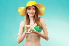 Mujer en el sombrero amarillo que lleva a cabo la c?scara blanca imagenes de archivo