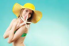 Mujer en el sombrero amarillo que lleva a cabo la c?scara blanca fotografía de archivo