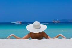 Mujer en el sombrero blanco que miente en la playa Foto de archivo