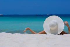 Mujer en el sombrero blanco que miente en la playa Foto de archivo libre de regalías