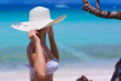 Mujer en el sombrero blanco que se coloca en la playa Fotografía de archivo