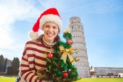 Mujer en el sombrero con viaje que se inclina cercano del árbol de navidad, Pisa de Papá Noel Fotos de archivo