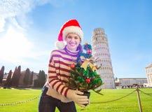 Mujer en el sombrero con viaje que se inclina cercano del árbol de navidad, Pisa de Papá Noel Fotos de archivo libres de regalías