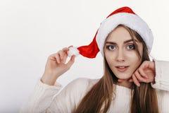 Mujer en el sombrero de la Navidad que mira la cámara Imagen de archivo libre de regalías