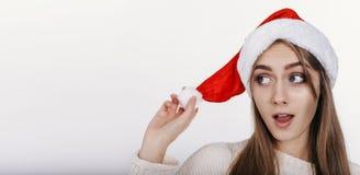 Mujer en el sombrero de la Navidad que mira de lado con la cara emocionada Foto de archivo