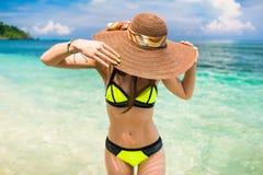 Mujer en el sombrero de la playa de las vacaciones que lleva que se baña en el océano fotos de archivo libres de regalías